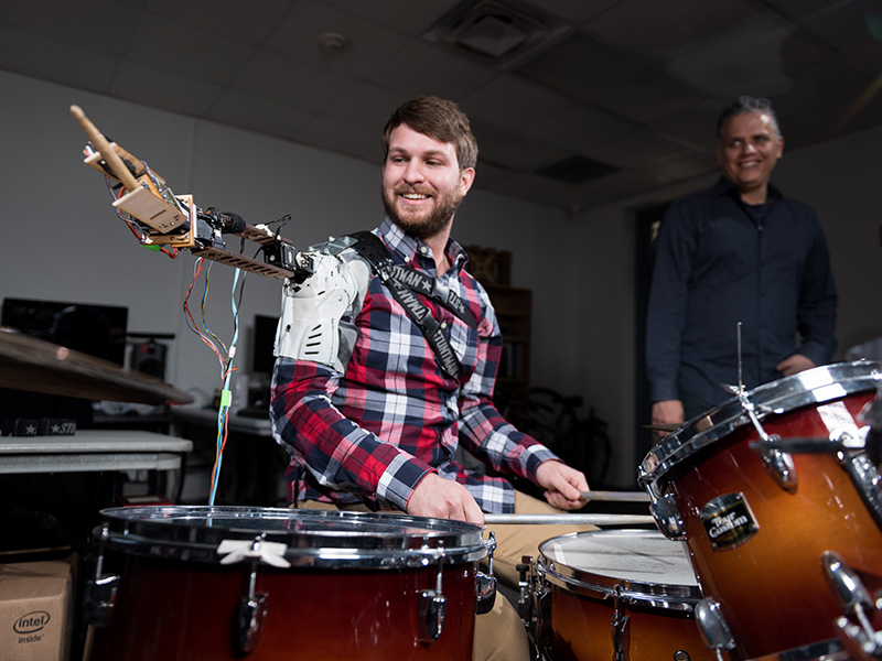 A man demonstrates the robotic third drumming arm.