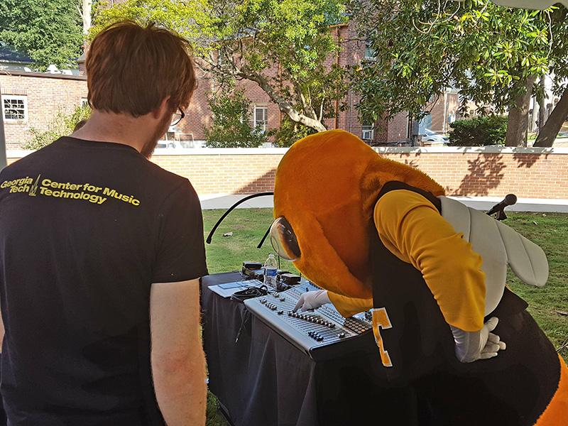Georgia Tech mascot Buzz examines a sound board on display.