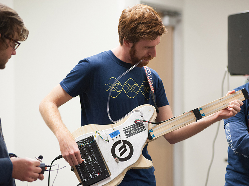 A man playing a modified guitar.
