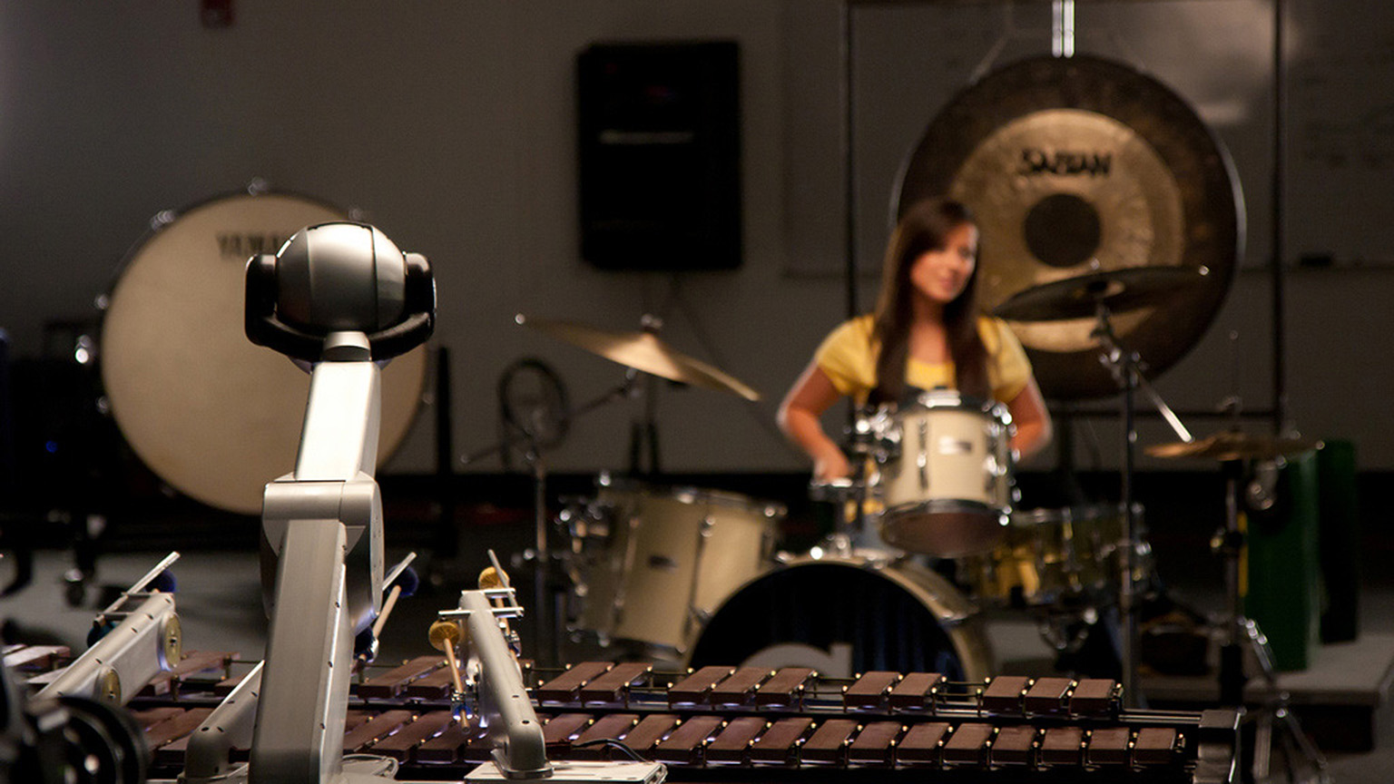 A woman performs on the drums as Shimon improvises with her.